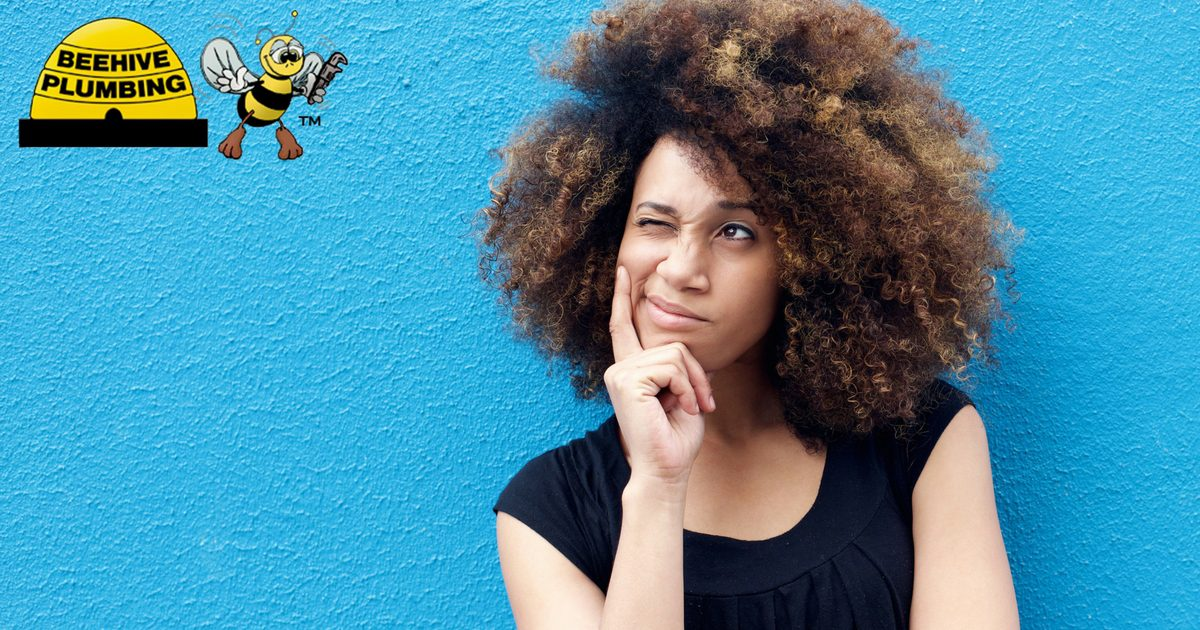 Woman Thinking Against Blue Wall Curly Hair - Solar Water Heater and Storage Tank Water Heater in Utah