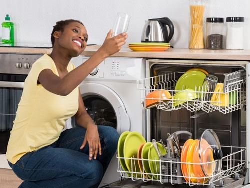 A woman holding a clean glass that recently went through the dish washer