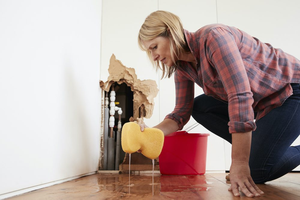 Worried woman mopping up water from a burst pipe with sponge